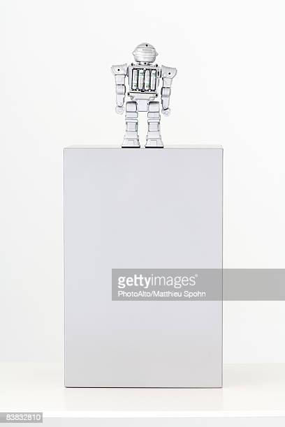 Toy robot standing on top of pedestal with batteries exposed, rear view