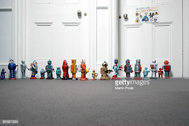 toy robots lined up outside childs bedroom - group of objects stock photos and pictures