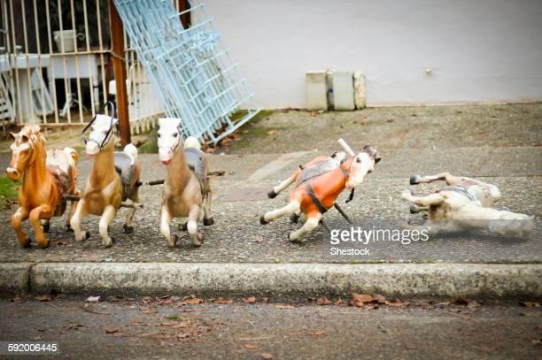 Toy rocking horses on city sidewalk