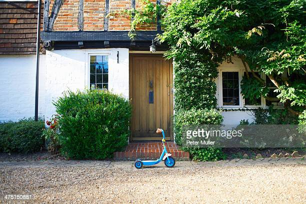 Toy scooter parked outside cottage