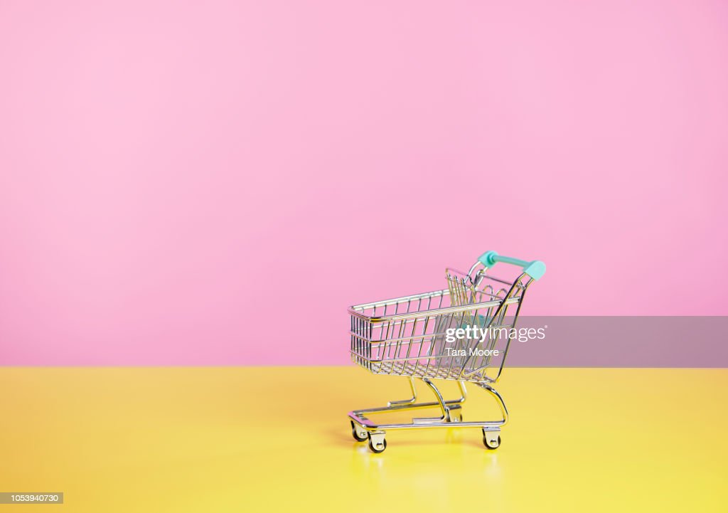 toy shopping trolley with pink  and yellow background : Stock Photo