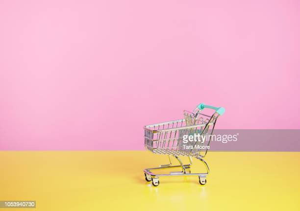 toy shopping trolley with pink  and yellow background - winkelen stockfoto's en -beelden