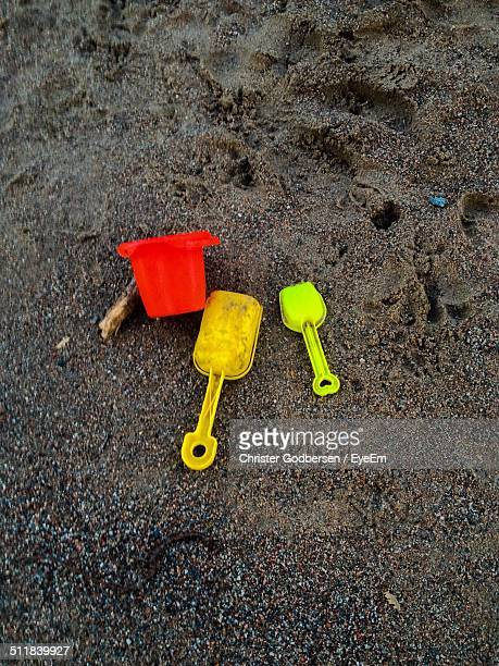Toy shovel and sandbox in sand on beach