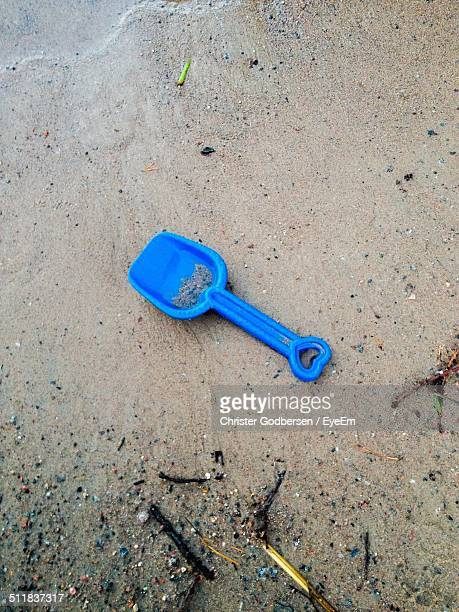 Toy shovel in sand on beach