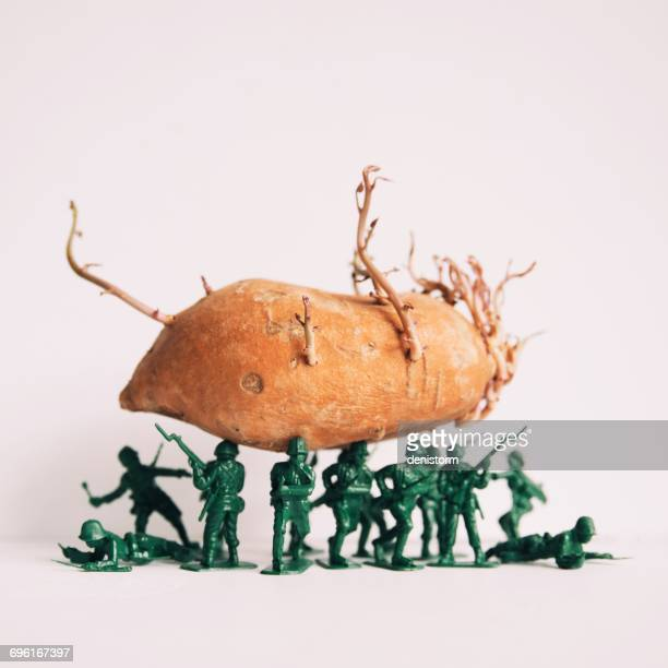 Toy soldier figures holding a sweet potato