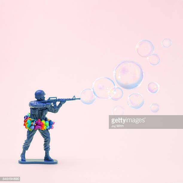 toy soldier shooting bubbles from gun - peace demonstration stock photos and pictures