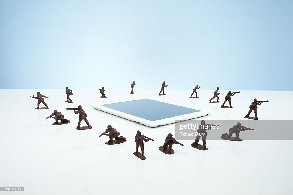 Toy soldiers in a 'firewall' around tablet : Stock Photo