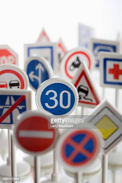 A toy speed limit sign surrounded by other various road warning signs