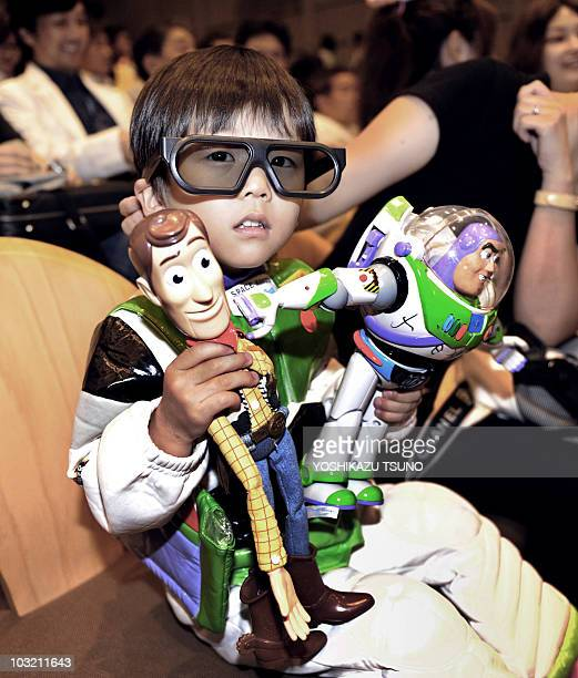 A Toy Story fan wears a special 3D glasses and holds his favorirte toys Woody and Buzz Lightyear as he enjoys Disney/Pixar's new 3D animation movie...