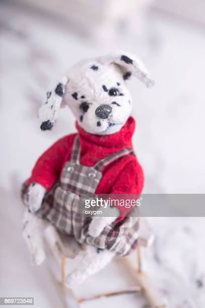 Toy Teddy Dog Dalmatian on a red sweater sitting on a sleigh