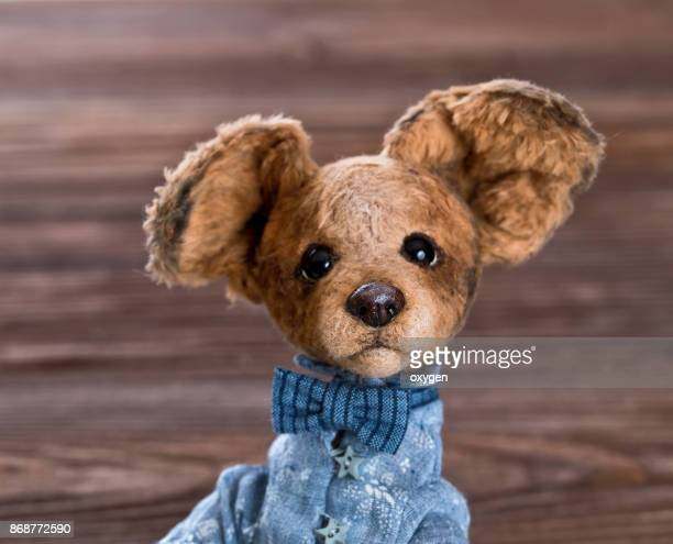 Toy Teddy Dog sitiing on a dark wooden background