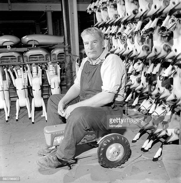 Man sitting on toy tractor at the Triang factory in Merton South London 1965
