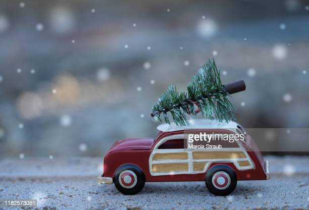 toy vintage sation wagon with wood panels and with christmas tree on snowy day - car decoration stock pictures, royalty-free photos & images