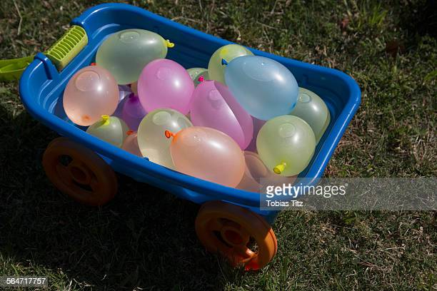 Toy wheelbarrow filled with water balloons at yard