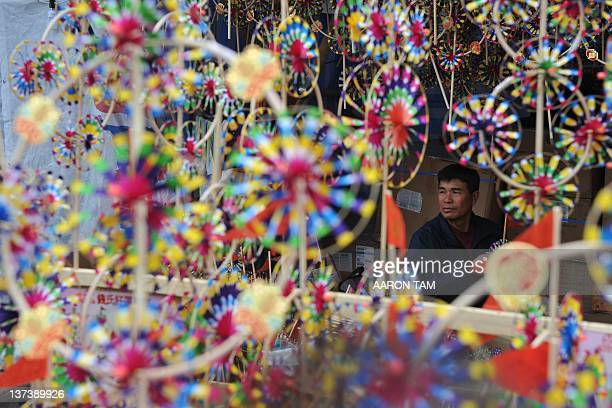A toy wind fan maker looks on at his store at Victoria Park during the Hong Kong Chinese New Year flower market on January 20 2012 The Chinese New...