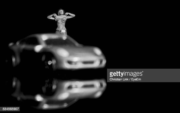 Toy Woman Showing Breasts By Car Against Black Background