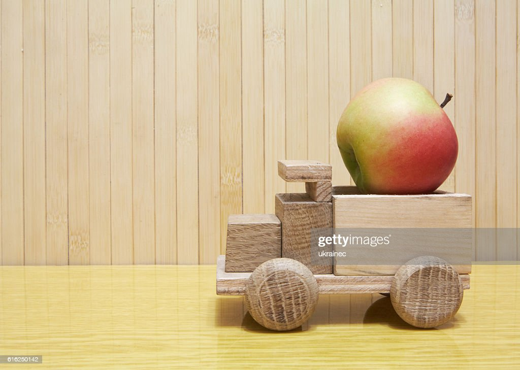 Toy wooden car with red apple : Foto de stock