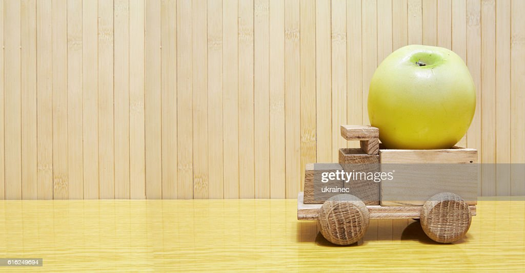 Toy wooden car with yellow apple : Foto de stock