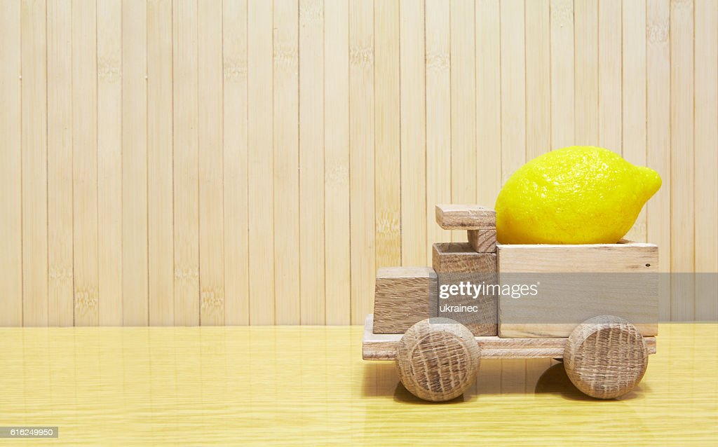 Toy wooden car with yellow lemon : Stock-Foto