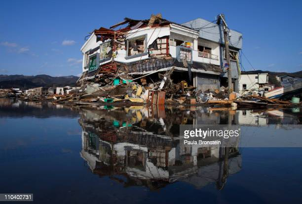 Toyoki Sugawara looks out from his destroyed liquor shop where he is collecting the items he can salvage on March 18 2011 in Kesennuma Miyagi Japan...