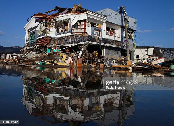 Toyoki Sugawara looks out from his destroyed liquor shop where he is collecting any items he can salvage on March 18 2011 in Kesennuma Miyagi Japan...