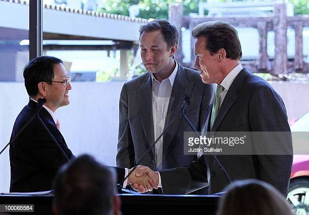 Toyota CEO Akio Toyoda Tesla Motors CEO Elon Musk and California governor Arnold Schwarzenegger shake hands during a news conference at Tesla Motors...