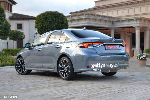 toyota corolla sedan in hybrid version on the street - toyota motor co stock pictures, royalty-free photos & images