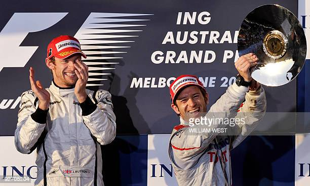 Toyota driver Jarno Trulli of Italy celebrates with his trophy after coming third as winner and Brawn driver Jenson Button of Great Britain looks on...