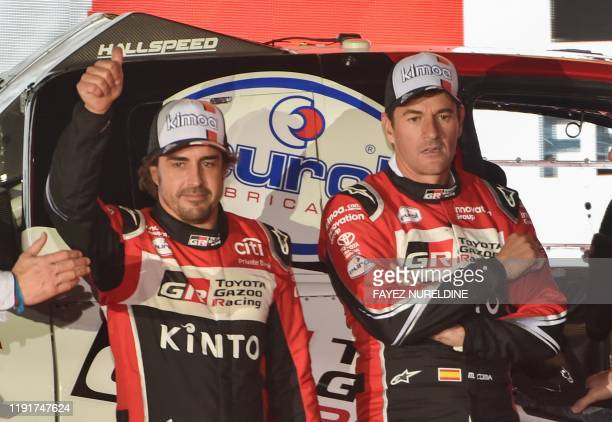 Toyota Gazoo Racing's Spanish driver Fernando Alonso gives the thumbs-up as his Spanish co-driver Marc Coma looks on during the podium ceremony in...