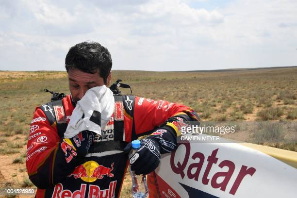 Toyota Hilux Qatari pilot Nasser Al Attiyah wipes his face during the fourth leg of the Silk Way Rally 2018 Astrakhan-Astrakhan on July 24, 2018.
