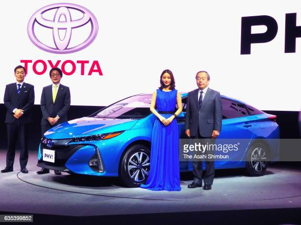 Toyota Motor Co Chairman Takeshi Uchiyamada and actress Satomi Ishihara stand next to the Prius New plugin hybrid 'PHV' during its unveiling at the...