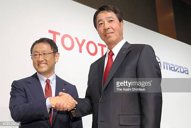 Toyota Motor Co President Akio Toyoda and Mazda Motor Co President Masamichi Kogai shake hands during a press conference on May 13 2015 in Tokyo...