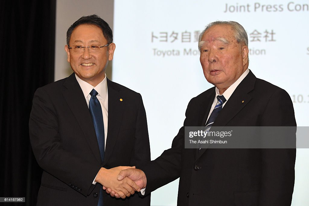Toyota Motor Co President Akio Toyoda (L) and Suzuki Motor Co Chairman Osamu Suzuki (R) shake hands during a joint press conference at the Toyota's Tokyo headquarters on October 12, 2016 in Tokyo, Japan. Automakers are in discussion on business partnership in the environment, safety, and information technology fields.