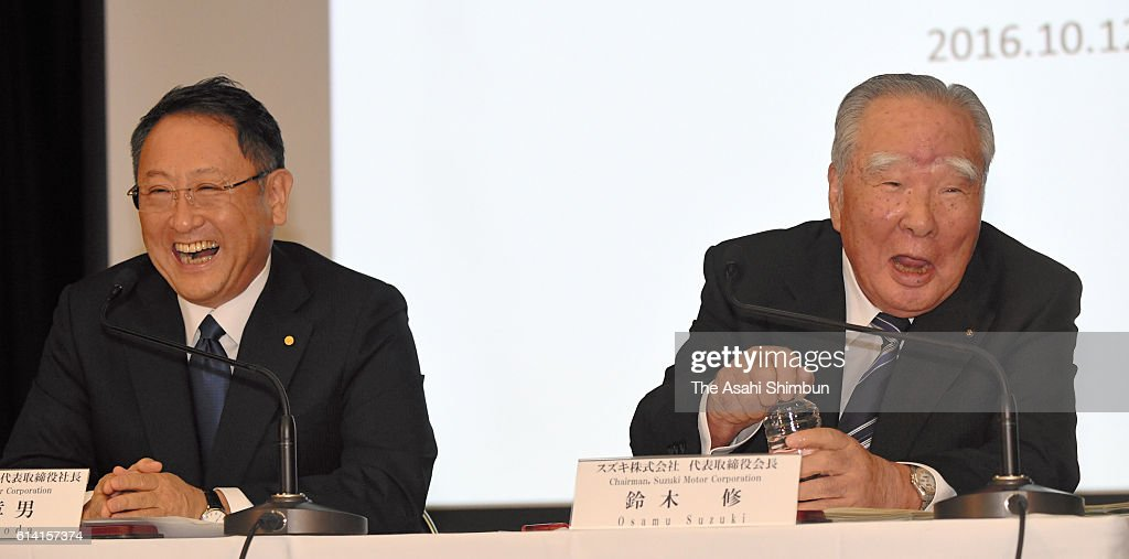 Toyota Motor Co President Akio Toyoda (L) and Suzuki Motor Co Chairman Osamu Suzuki (R) shake a laugh during a joint press conference at the Toyota's Tokyo headquarters on October 12, 2016 in Tokyo, Japan. Automakers are in discussion on business partnership in the environment, safety, and information technology fields.