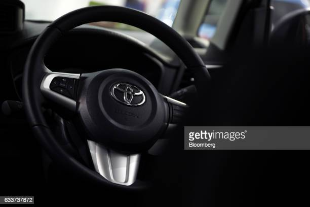 A Toyota Motor Corp badge is displayed on the steering wheel of a vehicle inside the Toyota City Showcase exhibit at the company's Mega Web car theme...