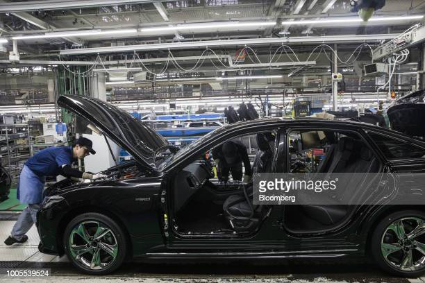 Toyota Motor Corp. Employees work on the Crown vehicle production line at the company's Motomachi plant in Toyota City, Aichi, Japan, on Thursday,...