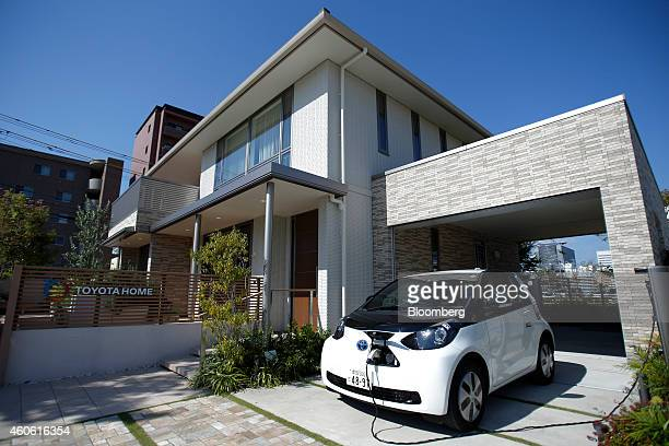 A Toyota Motor Corp eQ compact electric vehicle sits charging while parked outside a model smart home in Toyota's Ecoful Town in the Higashiyama...