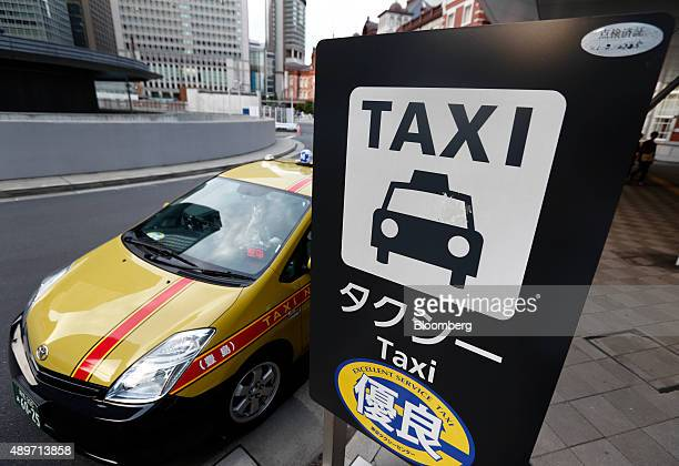 A Toyota Motor Corp Prius hybrid vehicle taxi sits parked while waiting for customers at a taxi stand outside a train station in Tokyo Japan on...