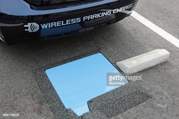 A Toyota Motor Corp Prius PHV plugin hybrid vehicle reverses to park over the company's wireless vehicle charging system which uses magneticresonance...