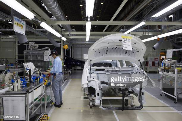 A Toyota Motor Corp worker assembles a Mirai fuelcell vehicle on the production line of the company's Motomachi plant in Toyota City Aichi Japan on...