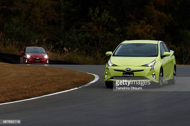 Toyota Motor Corp's fourthgeneration Prius prototype hybrid vehicles are driven during the test drive at the Fuji Speedway on November 12 2015 in...