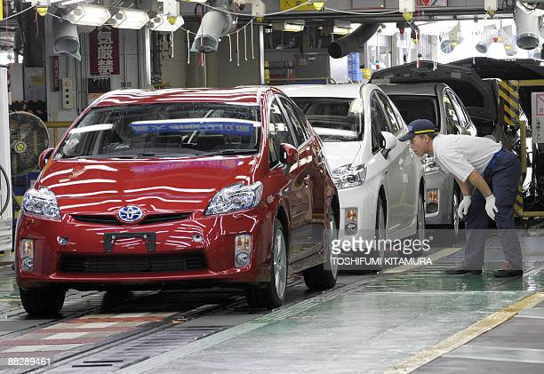 A Toyota Motors Tsutsumi factory worker checks the latest assembled Prius hybrid vehicle at the factory in Toyota city Aichi prefecture on June 35...