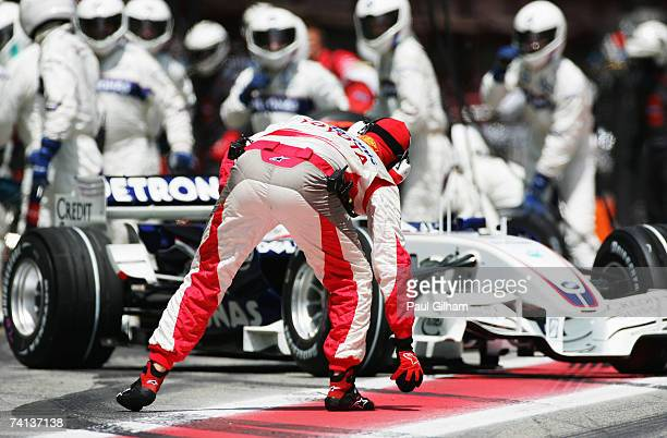 Toyota pitcrew member picks up a loose wheelnut in pitlane in front of Nick Heidfeld of Germany and BMW Sauber as he leaves his garage after a...