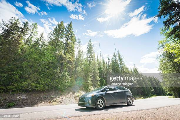 toyota prius hybrid car on road trip glacier national park - toyota motor co stock pictures, royalty-free photos & images