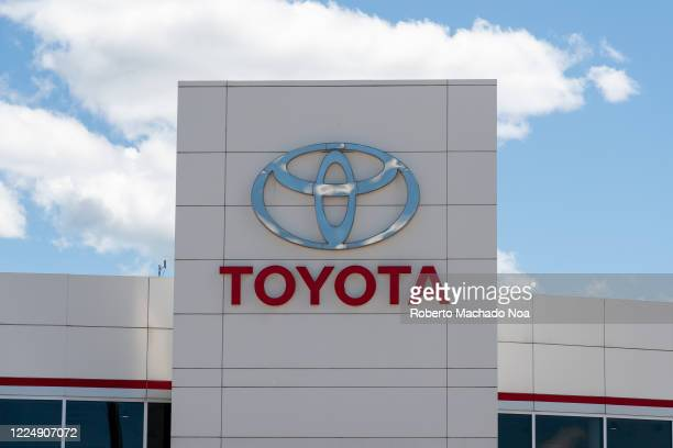 Toyota sign on car dealer during the daytime. The sky is blue with some clouds.