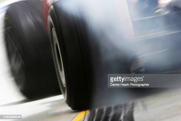 Toyota TF108 Formula One car leaves the Toyota pit stop box in the pit lane spinning its left rear Bridgestone tyre and producing blue burning rubber...