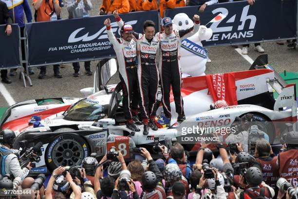 Toyota TS050 Hybrid LMP1 drivers Spain's driver Fernando Alonso Japan's Kazuki Nakajima and Switzerland's Sebastien Buemi celebrate after winning the...