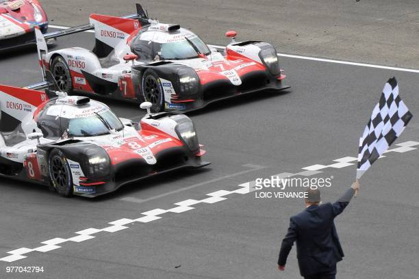 TOPSHOT Toyota TS050 Hybrid LMP1 Japanese's driver Kazuki Nakajima crosses the finish line to win ahead Toyota TS050 Hybrid LMP1 Japan's driven by...