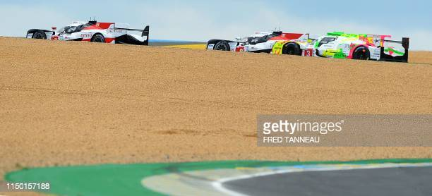 Toyota TS050 Hybrid LMP1 of British's driver Mike Conway leads ahead of by Toyota TS050 Hybrid LMP1 of Swiss 'driver Sebastien Buemi and Rebellion...