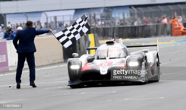 TOPSHOT Toyota TS050 Hybrid LMP1 of Japanese's driver Kazuki Nakajima crosses the finish line to win the 87th edition of the 24 Hours Le Mans...